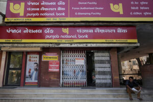A man reads a newspaper outside a branch of Punjab National Bank in Ahmedabad